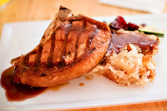 Lean Pork Chop Against The Potatoes And Top With Port Wine Sauce Sprinkle Some Cherries Around Plate Voila