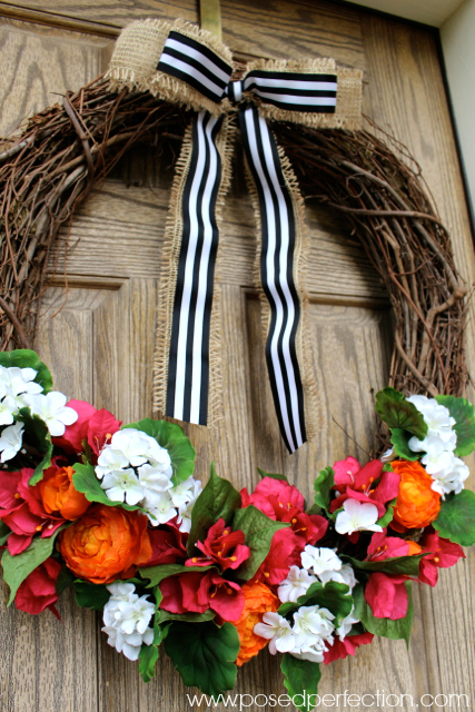 Bright blooms and a bold striped ribbon come together in this beautiful summer wreath.