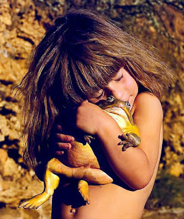 young girl hugging a very large bullfrog