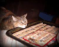 Preparing Scrabble tiles for upcycled jewelry with the assistant Sweet Pea, the cat.