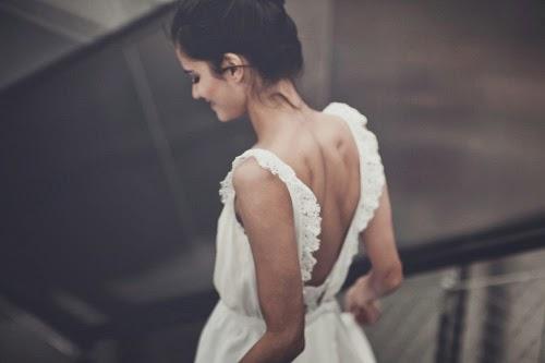 femme brune descendant les escalier, coiffure chignon jour de mariage, en robe de mariée laure sagazan blanche simple épurée moderne créateur de talent. Femme sexy
