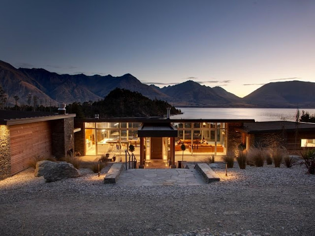 Glass house with the lake and mountains in the background