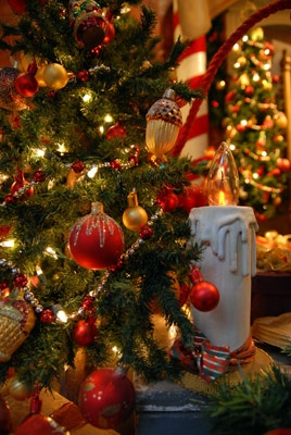 close up photo of decorated Christmas tree and white candle