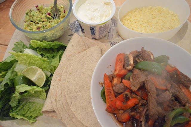 Steak fajitas with guacamole, salad and soured cream