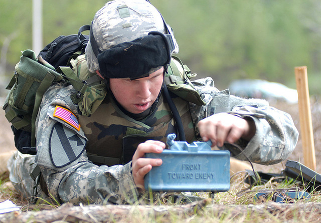 An American soldier carefully placing a claymore anti-personnel mine