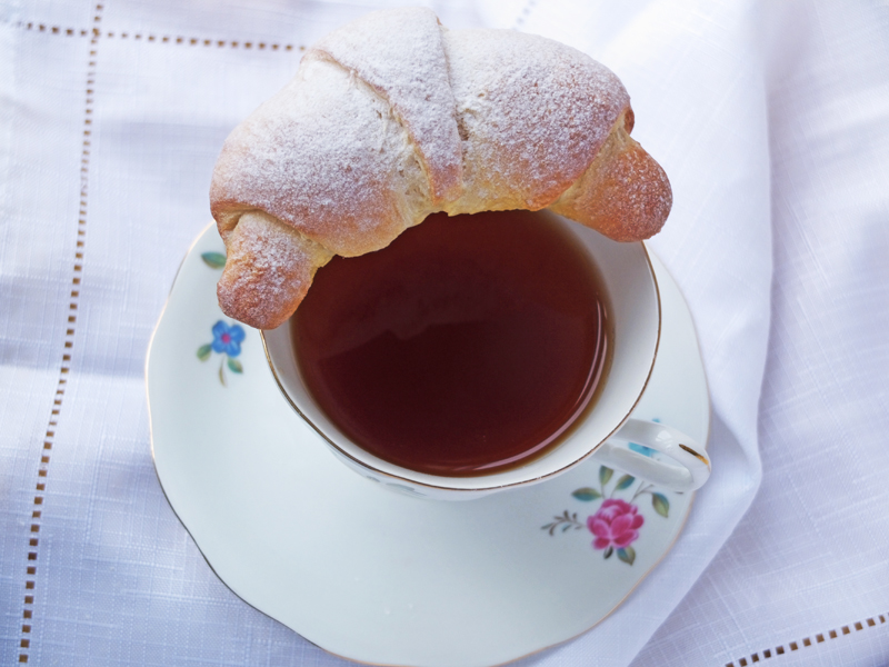 Nutella crescent dusted with icing sugar placed on a china tea cup.