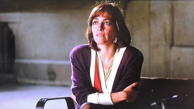 Pepa (Carmen Maura) wearing two cardigans and sitting on bench