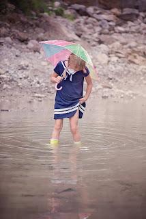 Kind mit Schirm und Gummistiefeln in Pfütze