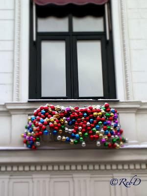 En mängd julgranskulor i olika färger under fönster på vit fasad. foto: Reb Dutius