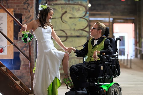 young woman in white wedding dress, holding the hand of groom, a young man in a wheelchair