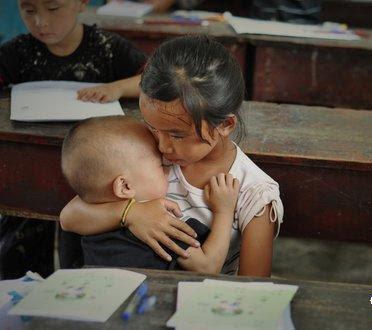 anak-kecil-sekolah-sambil-mengasuh-adiknya