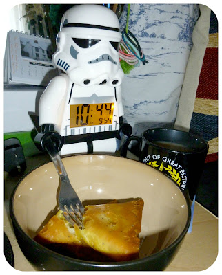 A LEGO stormtrooper alarm clock holding a fork over a bowl of samosas.