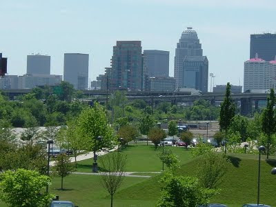 view of the river front park with trees and green grass and the downtown buildings in the background