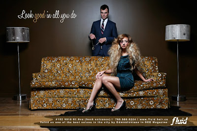 Hair Salon ad - woman with black eye sitting on couch, man behind her holding large diamond necklace