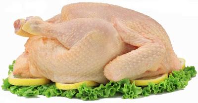 Un pollo crudo sobre hojas de lechuga y rodajas de limón