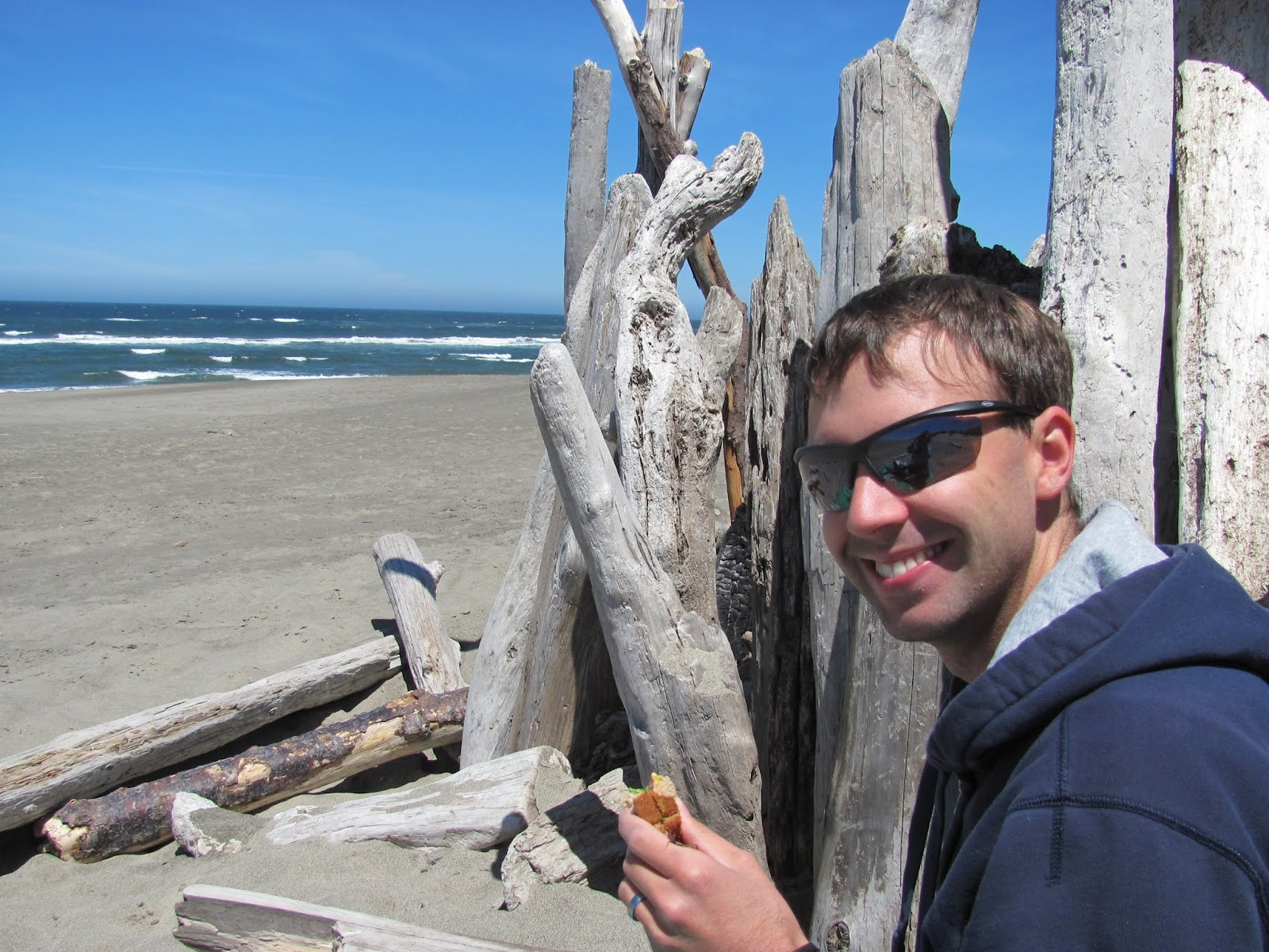 Cory eats a sandwich behind a pile of driftwood and eats a sandwich at Bullards Beach State Park, Oregon