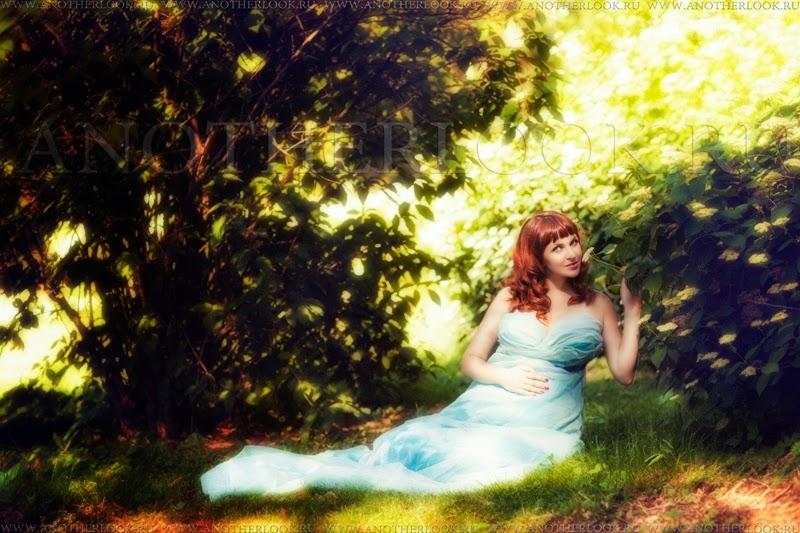 беременная девушка сидит под кустом в голубом платье