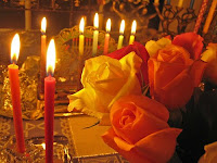 Lit candles with yellow and white roses