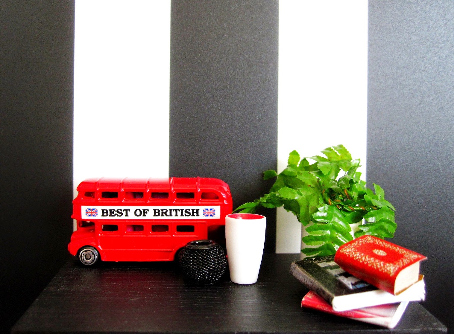 Modern miniature black table displaying a model London bus, vases, books and a plant in black, white and red.