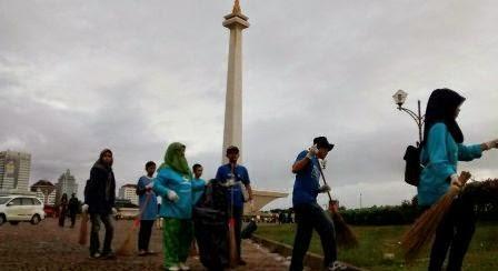 relawan membersihkan sampah perayaan tahun baru du monas