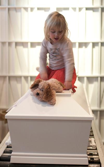Tre-årig lille pige leger med bamser, på låget af sin mors kiste - fra udstillingen Memento Mori, Vor Frue Kirke
