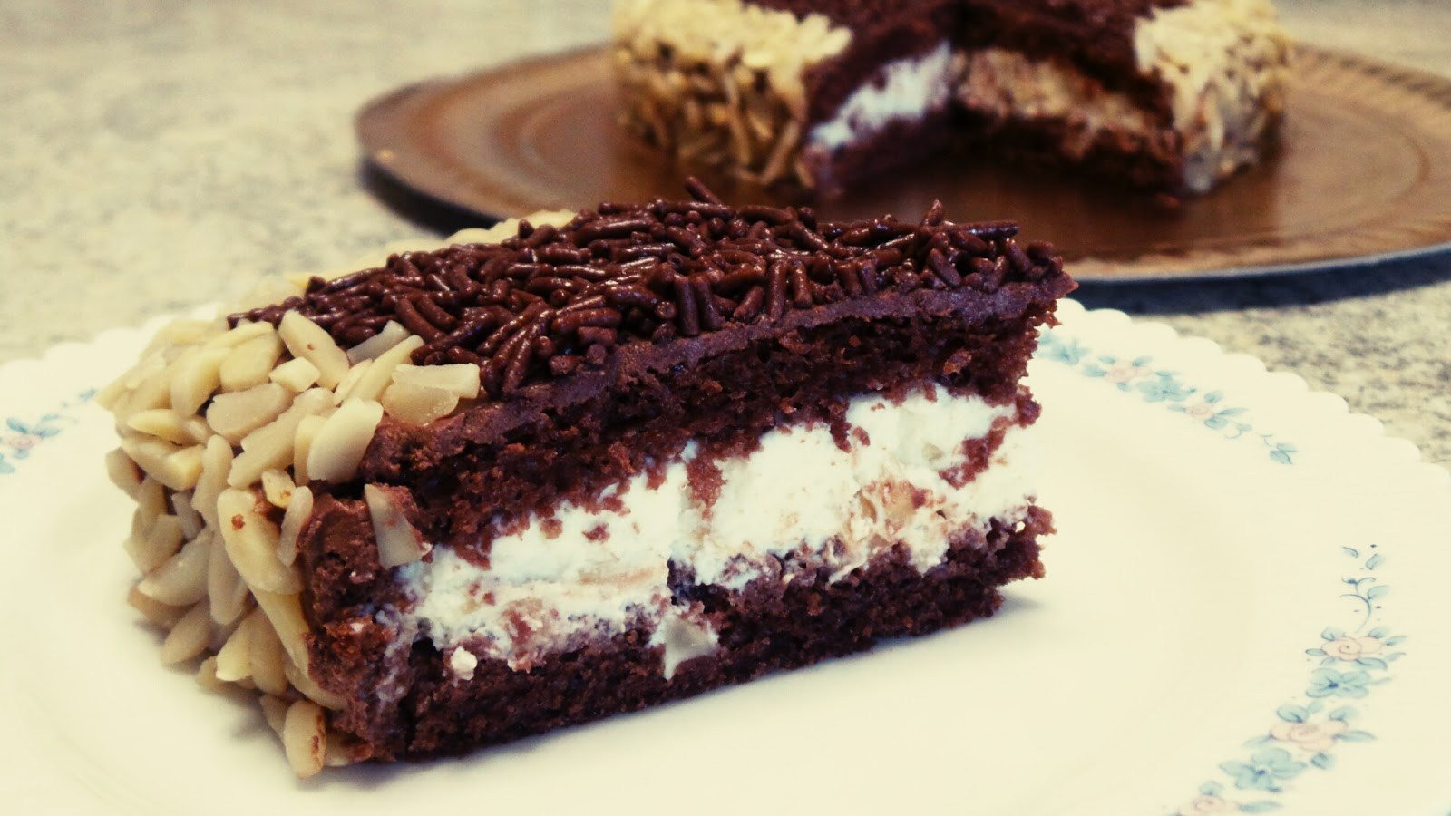 Torta alle mandorle e cioccolato a forma di cuore con farcia di ricotta e nocciole e copertura allo yogurt greco