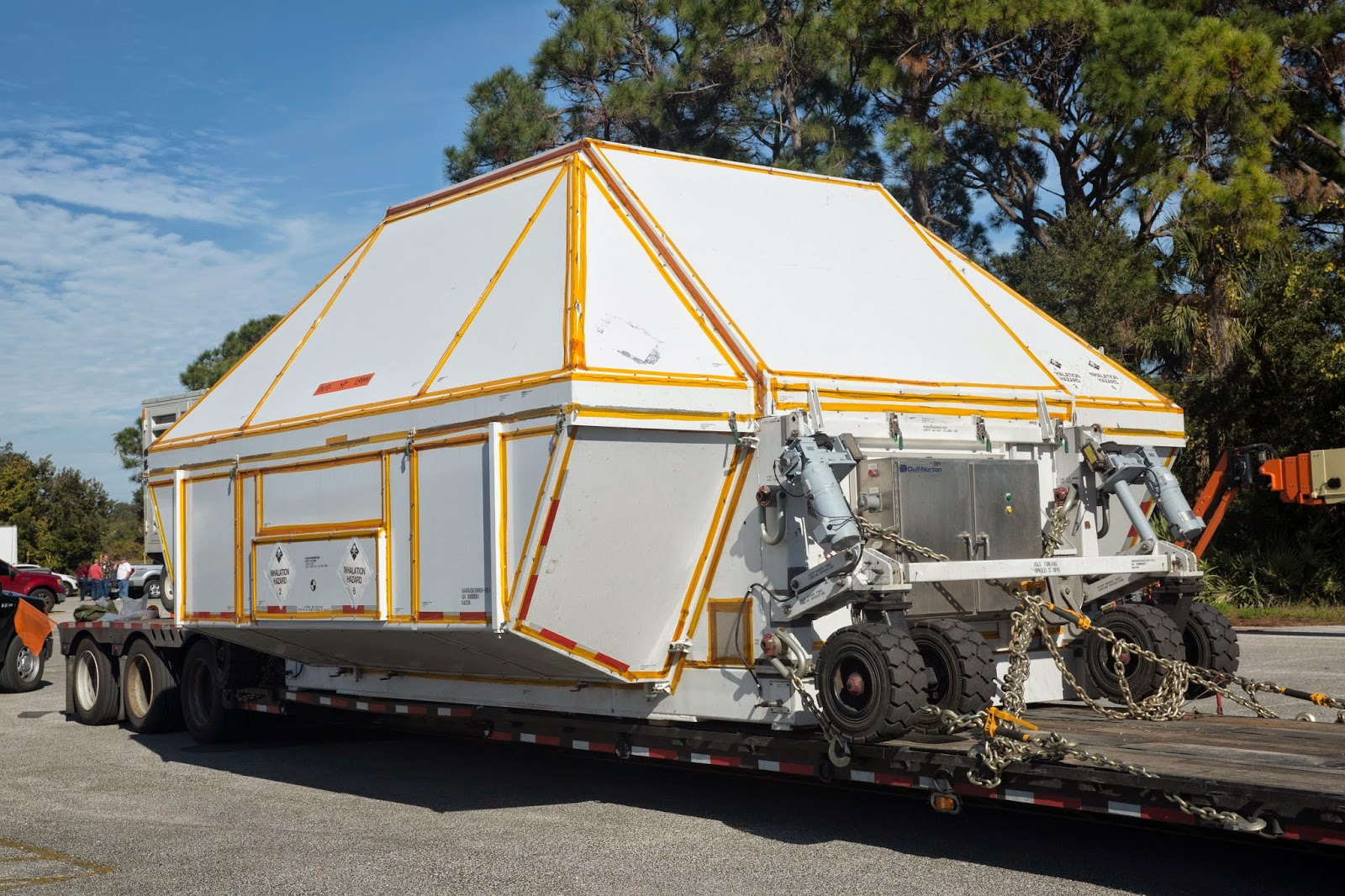 NASA's Orion crew module, enclosed in its crew module transportation fixture and secured on a flatbed truck approaches the Kennedy Space Center. Credit: Lockheed Martin