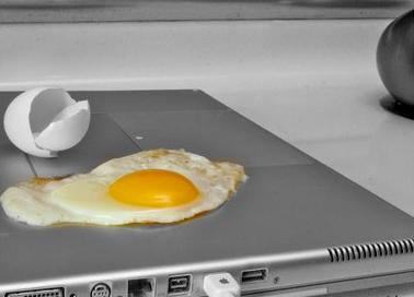 Egg being cooked on laptop processor