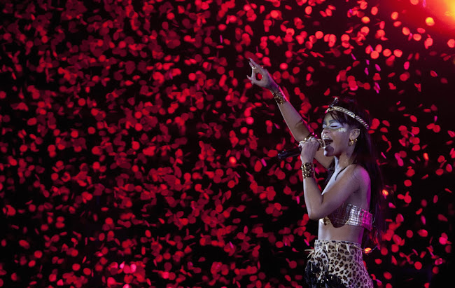 amazing photo with Rihanna Performing at the Robin Hood Foundation Benefit 2012 with millions of red flowers flying in the background