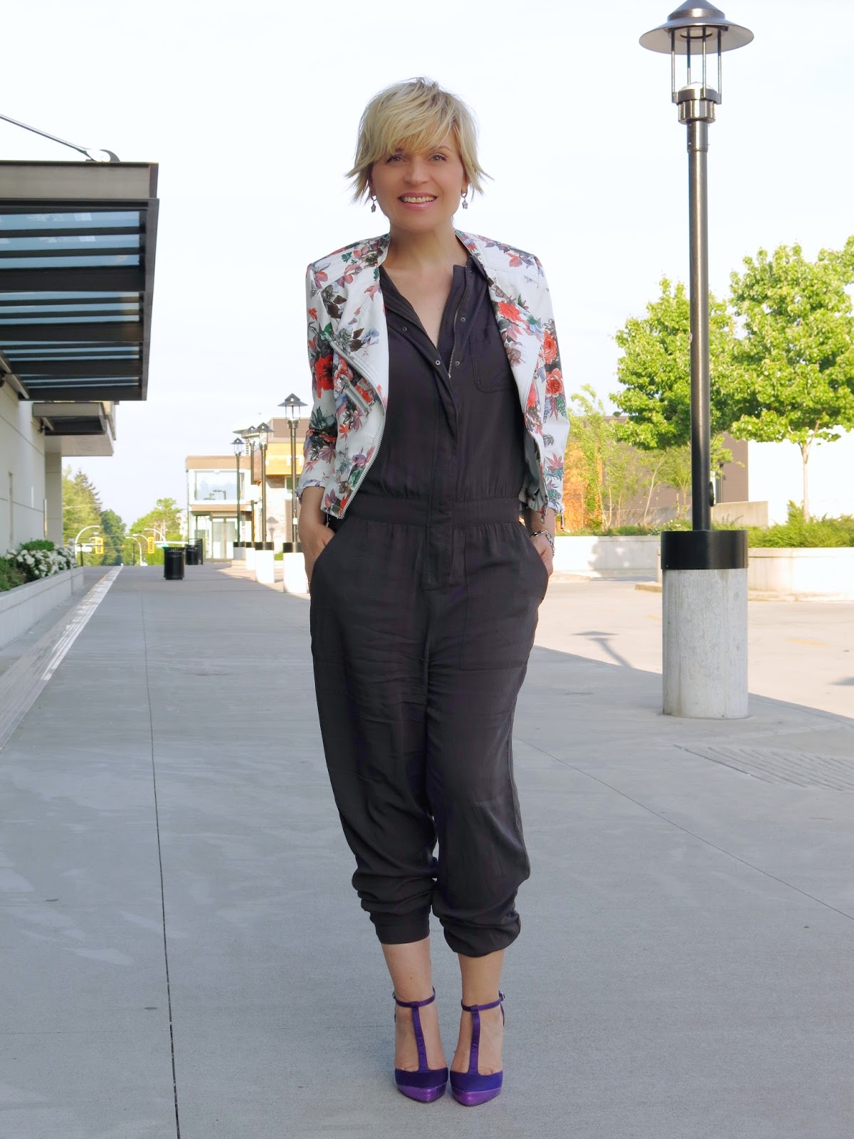 styling a jumpsuit with a floral moto jacket and purple t-strap shoes