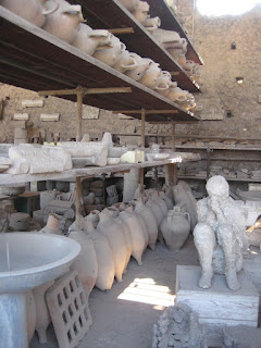 Artifacts and the body cast of a crouching Pompeii citizen.