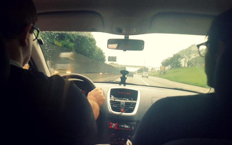 Na capa: Foto tirada do banco de trás de um carro pegando as costas do motorista e do meu irmão ao lado, o vidro do carro está salpicado de chuva e além dele a estrada a frente com algumas carros e gramado verde do lado