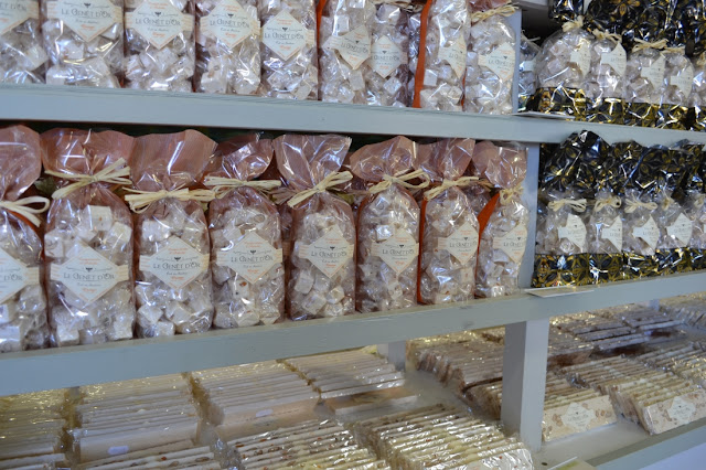 Zakken met diverse smaken in plastic gepakte stukjes nougat in een zak op een rek in de winkel bij de nougatier. In de onderste stellingen liggen nog in plastic gepakte plakken nougat