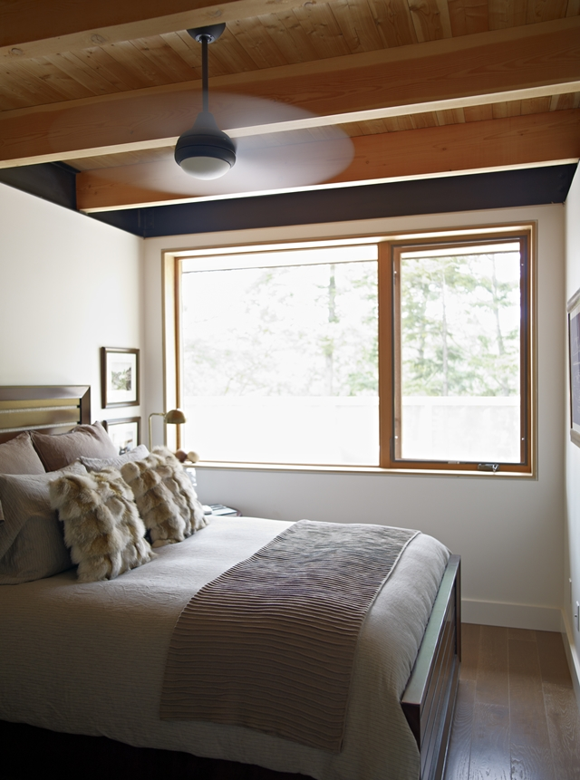Photo of small bedroom with the bed by the window of the forest house