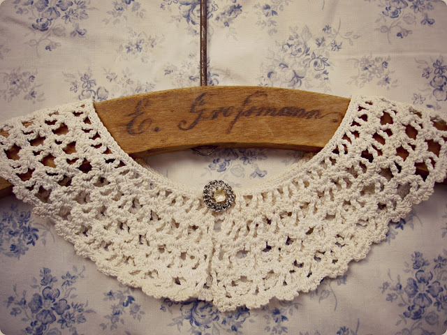 vintage crochet collar displayed on wood hanger
