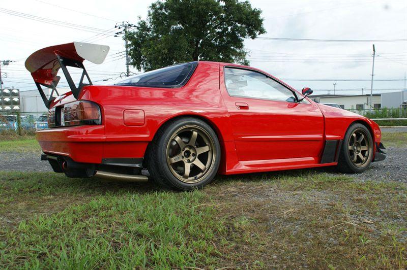 Mazda RX-7 FC, czerwona, z boku, brązowe felgi, duży spojler, ciekawe sportowe samochody z lat 80, auta z duszą
