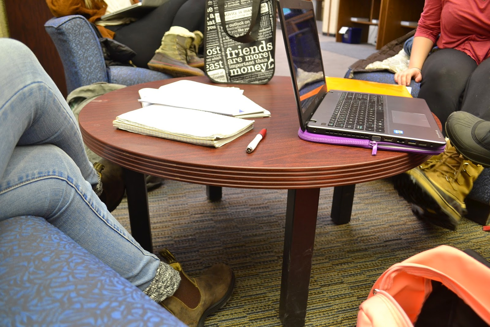 Image of people sitting around a round table.  Focus is on the open note book and laptop on table.