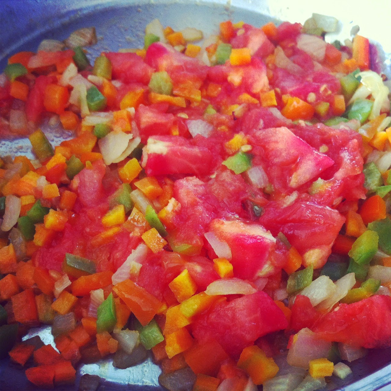 Friendo ajo, cebolla, pimientos y zanahoria.