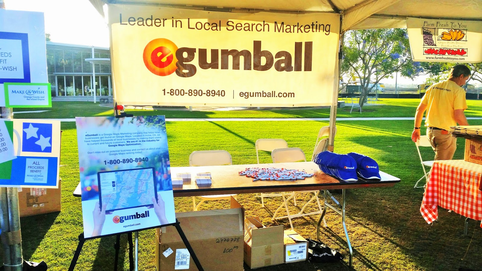 An eGumball, Inc. banner with the company's phone number and a table featuring business cards, pens, and eGumball hats.