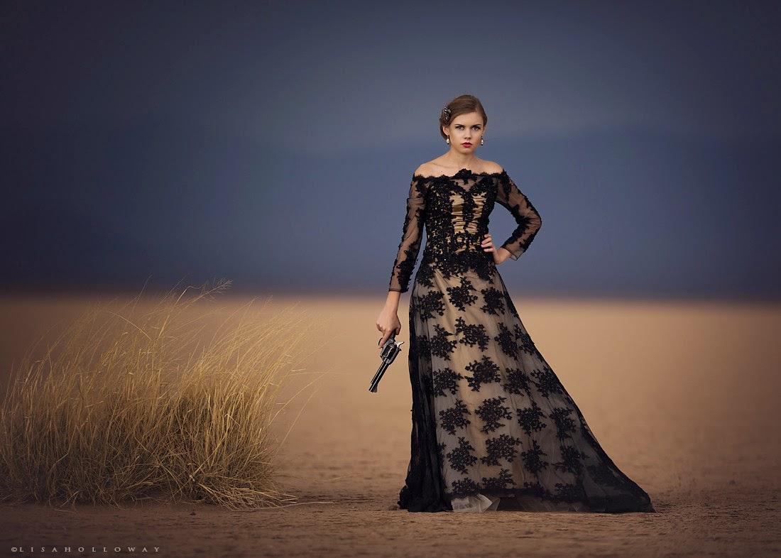 photo de Lisa Holloway représentant une jeune femme en robe noire en dentelle tenant un ancien revolver à la main dans un désert