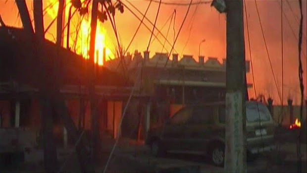 In this image taken from video, flames rise in the background of houses after a state-owned gas pipeline exploded in Nagaram village, in the southern Indian state of Andhra Pradesh Friday, June 27, 2014. A top official of the state-run Gas Authority of India Ltd, said more than a dozen people died in the fire following the explosion in the pipeline.