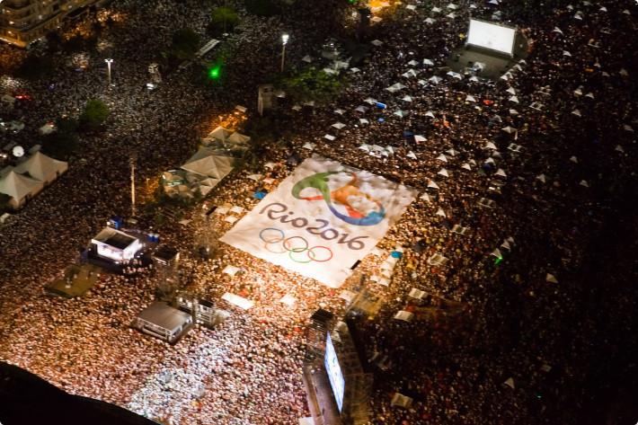 Bandeirão com a marca dos Jogos Olímpicos Rio 2016 foi aberto sobre a multidão na praia de Copacabana, no Rio. Foto: Thor Unamar