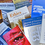A pile of books and journal articles published by the faculty.