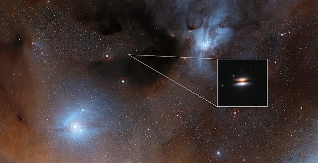 The young star 2MASS J16281370-2431391 lies in the spectacular Rho Ophiuchi star formation region, about 400 light-years from Earth. It is surrounded by a disc of gas and dust — such discs are called protoplanetary discs as they are the early stages in the creation of planetary systems. This particular disc is seen nearly edge-on, and its appearance in visible light pictures has led to its being nicknamed the Flying Saucer.  The main image shows part of the Rho Ophiuchi region and a much enlarged close-up infrared view of the Flying Saucer from the NASA/ESA Hubble Space Telescope is shown as an insert.  Credit: Digitized Sky Survey 2/NASA/ESA