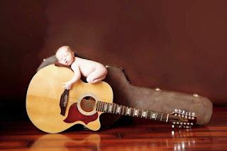 Gratis foto bayi lucu tidur di atas gitar