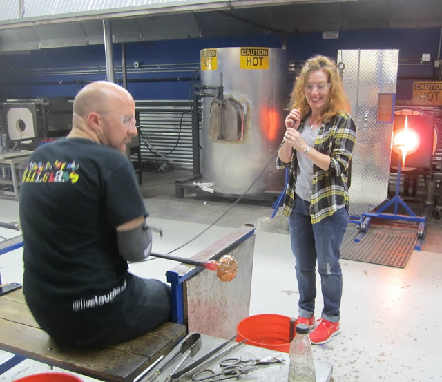 Fizzy Party turning glass into a pumpkin at glass blowing class