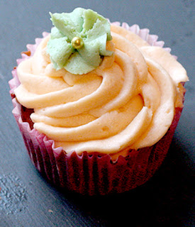 Sweet potato cupakes with an orange buttercream icing decorated with a green paste flower