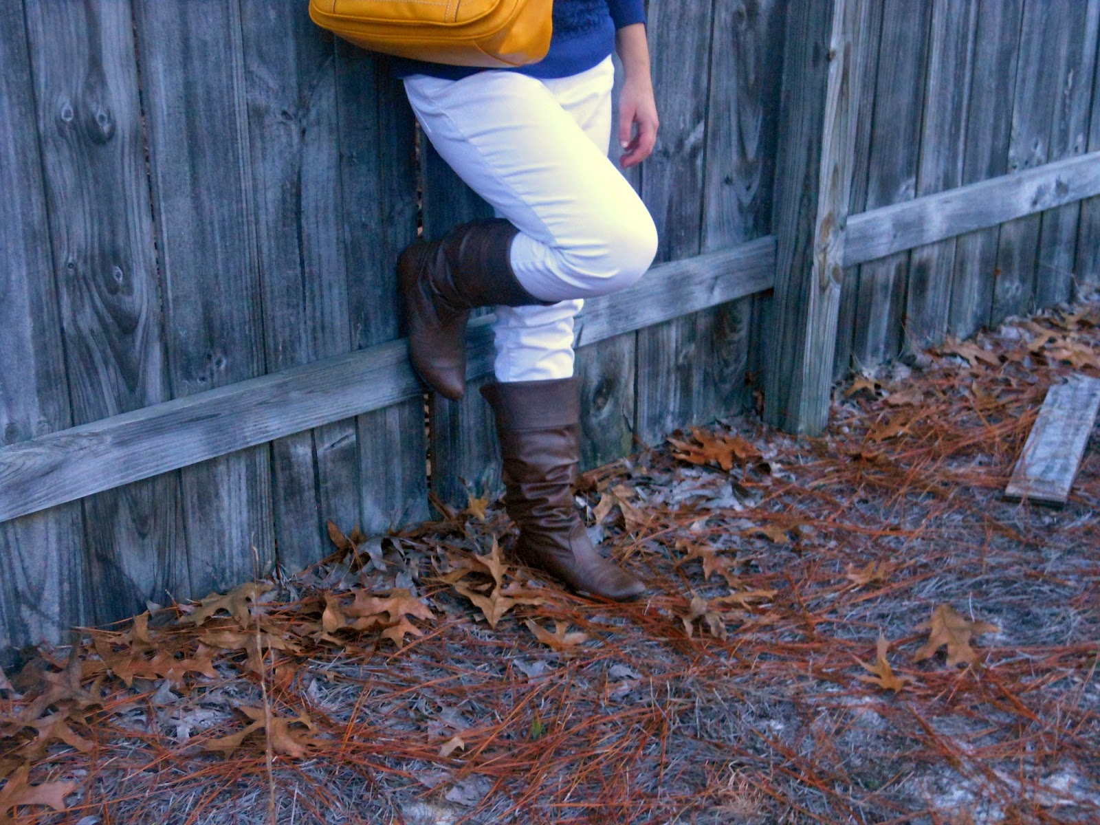 Mustard and Navy. Navy lace top, white jeans, brown boots, mustard bag, gold jewelry