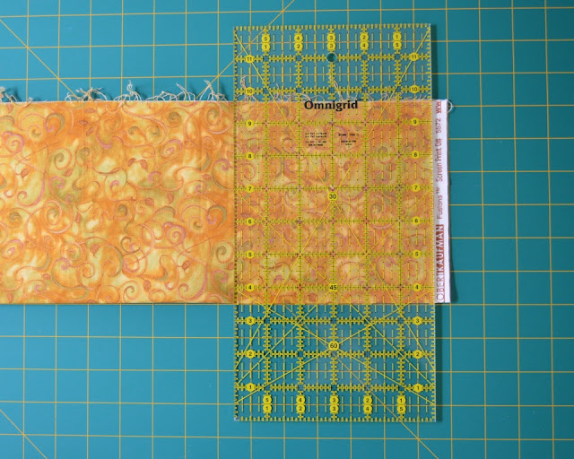 Fabric laid out on cutting mat. A quilter's rule is laid out on top, lined up with the mat grid, ready to trim off the selvage