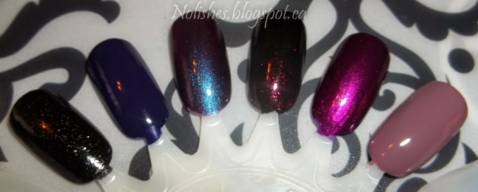 Goth is a black polish with small silver pieces of glitter, Wild Wisteria is a dark blurple, Royal Velvet is a medium purple/shimmery light blue duotone, Darkest Shadow is a black polish with a dark red fleck, Close Your Eyes is a shiny medium purple/plum, Blend is a greyish, purpley, brown mixed shade